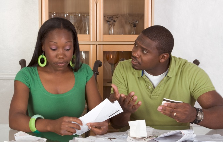 Image: Young couple  and trying to working through pile of bills
