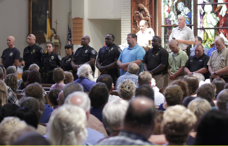 Image: Police officers attend a vigil after a fatal shooting of Baton Rouge policemen, at Saint John the Baptist Church in Zachary