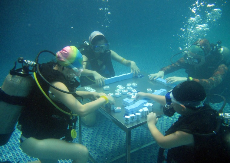 Image: Divers play mahjong in a swimming pool during a hot summer day in Chongqing