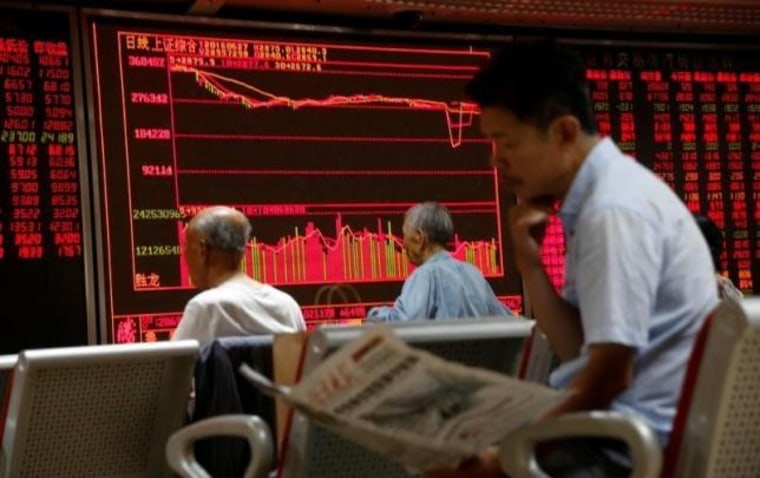 A man reads a newspaper in front of an electronic board at a brokerage house in Beijing