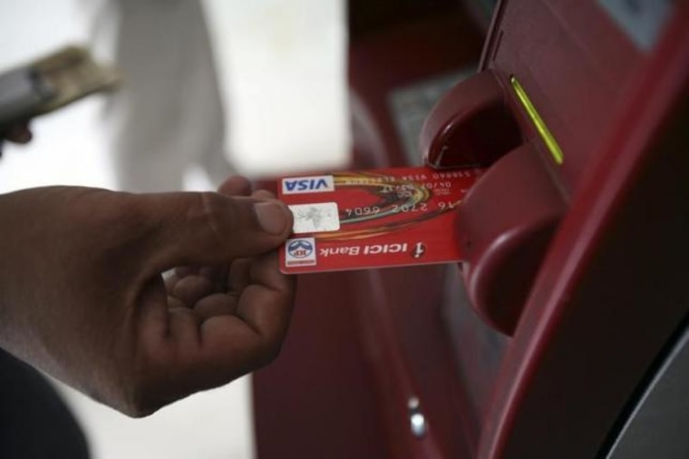 A customer uses his card to withdraw money from an ATM in Jammu
