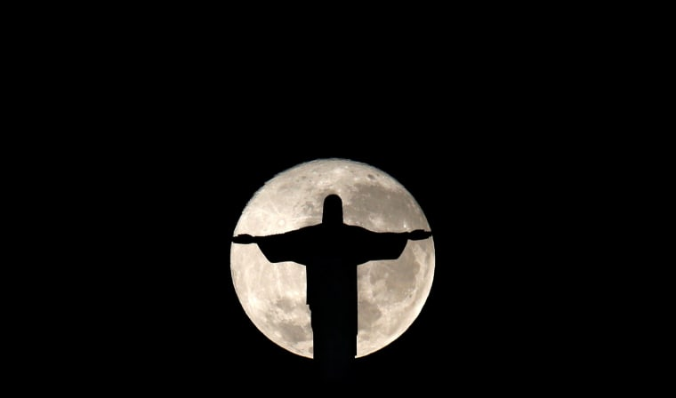 Image: The full moon is pictured behind the Christ the Redeemer statue ahead of the 2016 Rio Olympic games in Rio de Janeiro