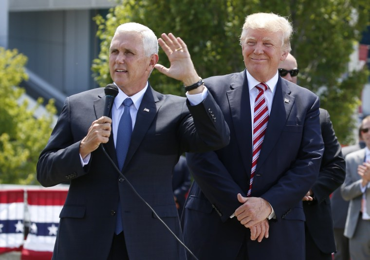 Image: Republican U.S. presidential candidate Trump listens to  Pence after arriving in Cleveland, Ohio