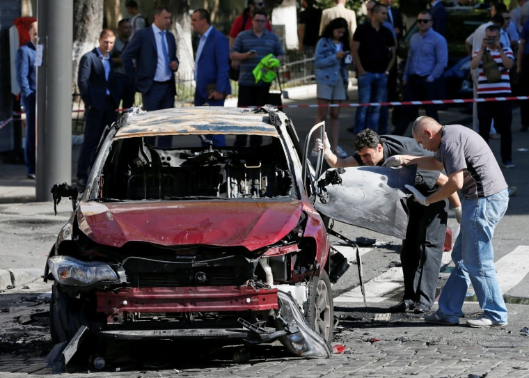 Image: Investigators inspect a damaged car at site where journalist Pavel Sheremet was killed by a car bomb in Kiev