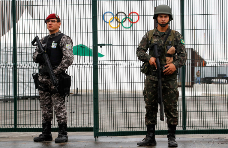 Image: Brazilian Public-Safety National Force and military police soldiers guard an entrance at the security fence outside the 2016 Rio Olympics Park in Rio de Janeiro