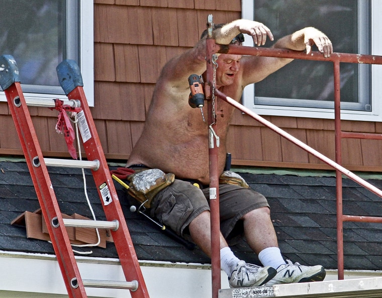 Jim Darnell, of Darnell Home Improvement, waits in the shade as a co-worker cuts another piece of siding for a home improvement job on July 21, 2016, in Quincy, Ill. Outdoor workers had to take more breaks than usual with the temperature in the upper 90's and the heat index in the 100s.