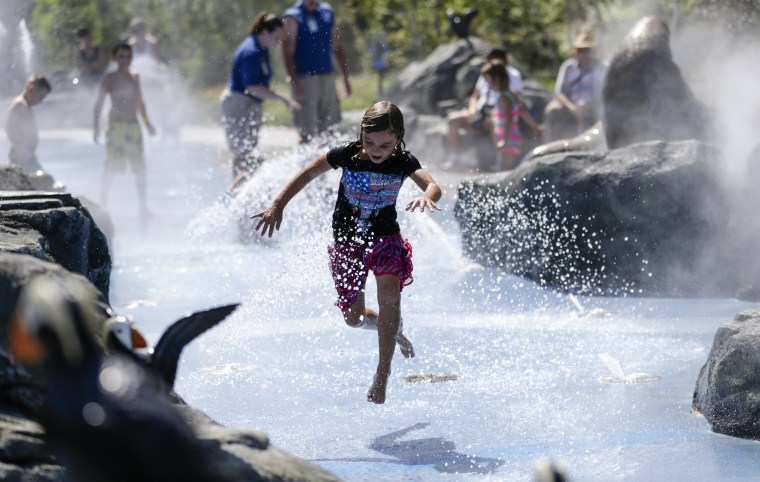 A child cools off at the Alaskan Adventure splash pad at the Henry Doorly Zoo in Omaha, Neb., on July 21, as high temperatures and humidity affect much of the central U.S., making it feel as hot as 115 degrees Fahrenheit in some places and leading some cities to open cooling stations and take other precautions.
