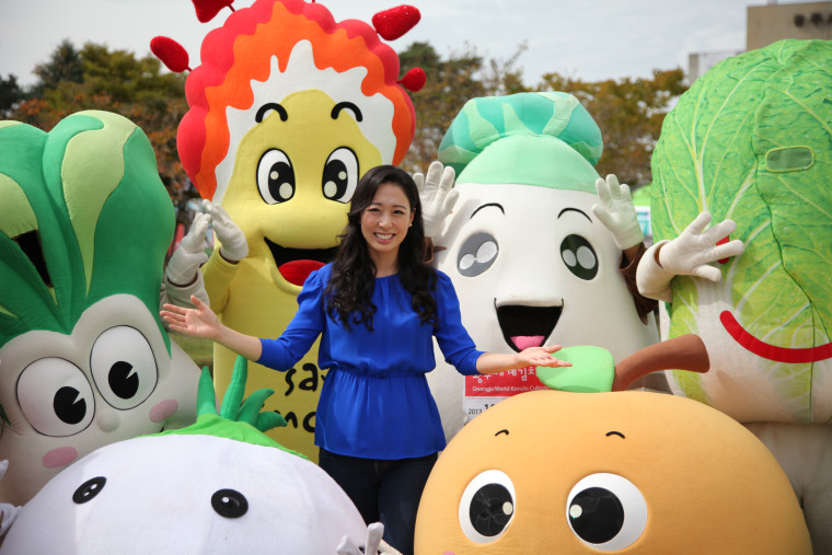 Judy Joo posing with characters representing traditional kimchis at the 2013 Gwangju World Kimchi Festival.