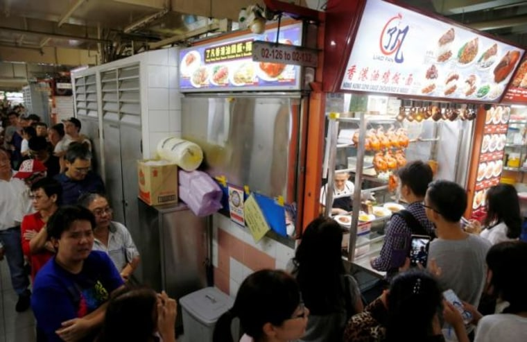People queue outside hawker Chan Hong Meng's Michelin star awarded stall, for his soya sauce chicken rice and noodle at a food market in Singapore