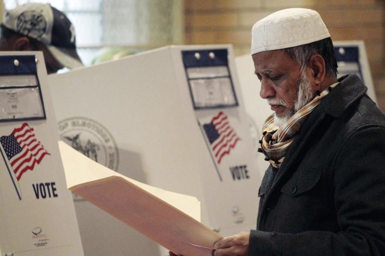 Kamal Pasha, originally from Bangladesh, reads over his ballot at a polling station in the Kensington neighborhood of Brooklyn on Nov. 5, 2013.