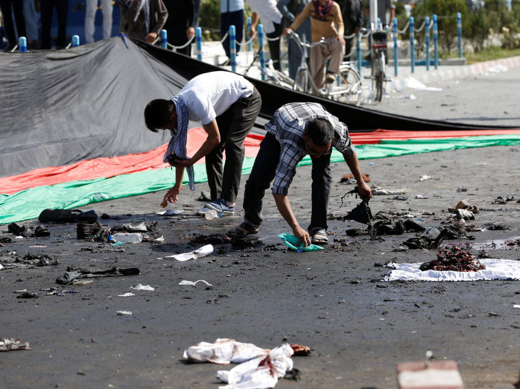 Image: Afghan men remove the remained clothes of victims from the ground after a suicide attack in Kabul