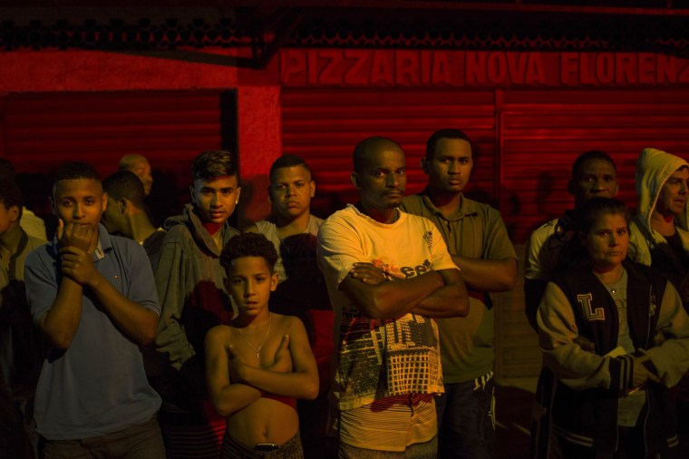 Image: Residents watch as police work a crime scene in greater Rio de Janeiro