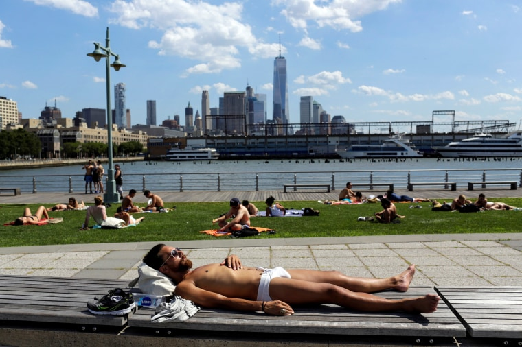 """Image: People take a sunbath during a heat wave called """"Heat Dome"""" in the Manhattan borough of New York, U.S."""