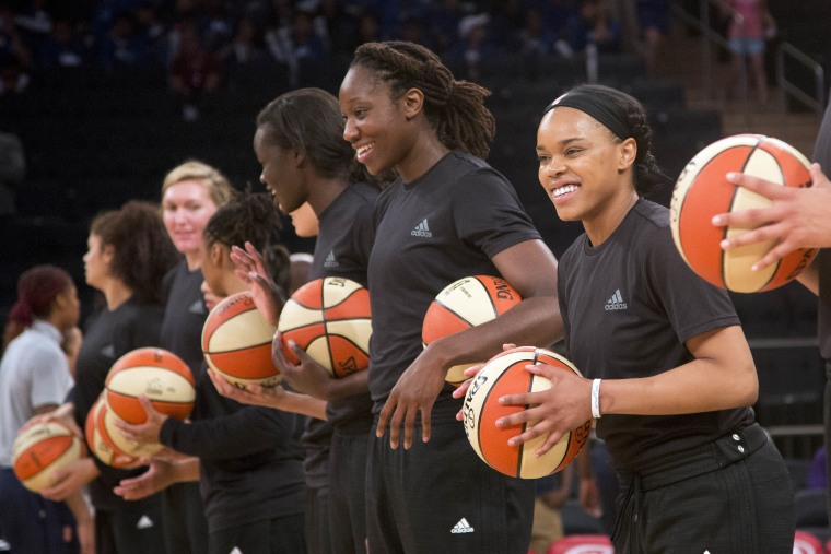 Members of the New York Liberty basketball team await the start of a game against the Atlanta Dream, Wednesday, July 13, 2016 in New York. Between the Black Lives Matter movement, the Orlando shooting and the LGBT community, more WNBA players have been taking active roles in expressing their views on social issues. In the midst of Camp Day? at the New York Liberty's mid-morning game Wednesday, Liberty players stood in solidarity as they donned all-black warmups in support of the Black Lives Matter movement.