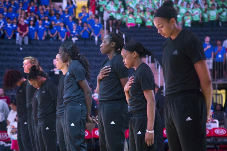 """Members of the New York Liberty basketball team stand during the playing of the Star Spangled Banner prior to a game against the Atlanta Dream, Wednesday, July 13, 2016 in New York. In the midst of """"Camp Day""""?? at the New York Liberty's mid-morning game Wednesday, Liberty players stood in solidarity as they donned all-black warmups in support of the Black Lives Matter movement."""