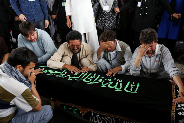 Image: Men mourn over the coffin of a victim a day after a suicide attack in Kabul, Afghanistan