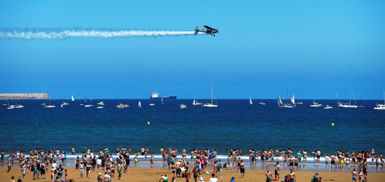 Image: A Cessna L19 Bird Dog flies over San Lorenzo beach during an aerial exhibition in Gijon