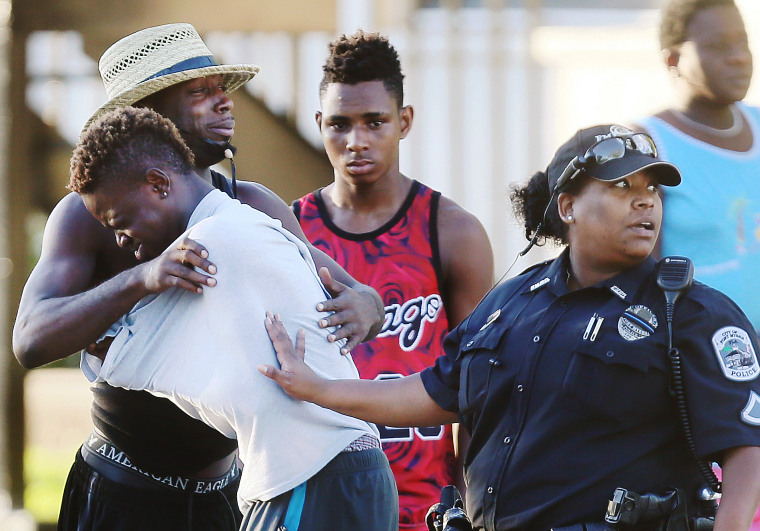 People embrace after a fatal shooting at Club Blu in Fort Myers, Fla., on July 25, 2016.