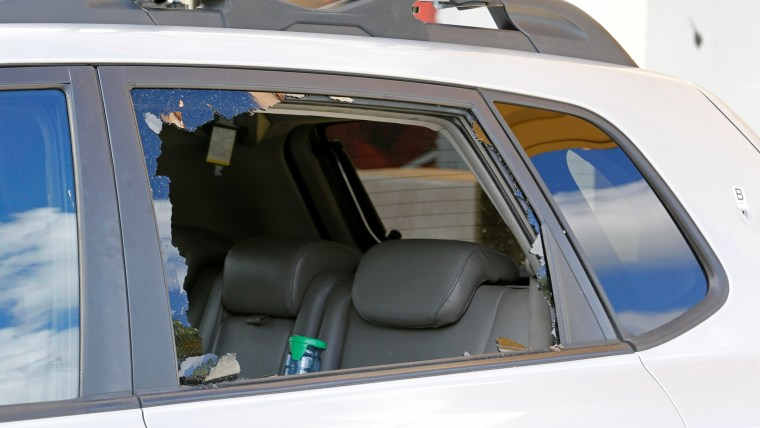 Image: The shattered window of a vehicle is shown in the parking lot of Club Blu after a shooting in Fort Myers