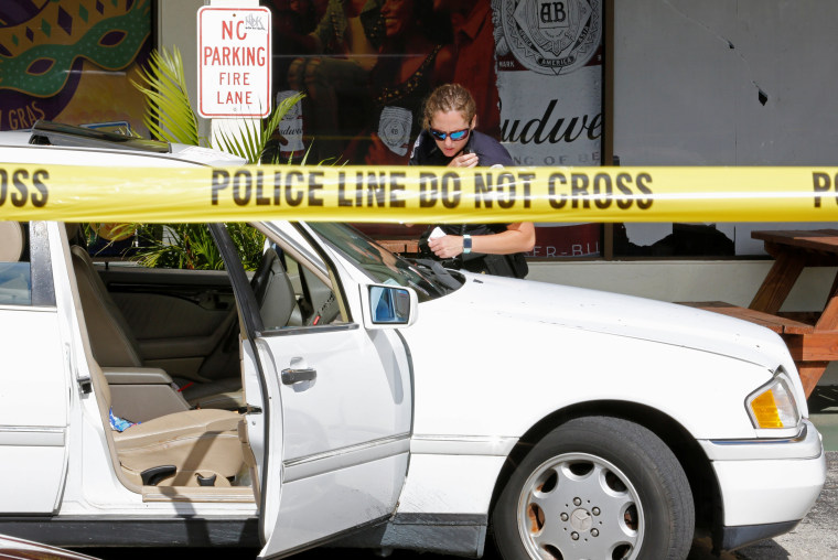 Image: A Fort Myers police officers examines a vehicle in the parking lot of Club Blu after a shooting in Fort Myers