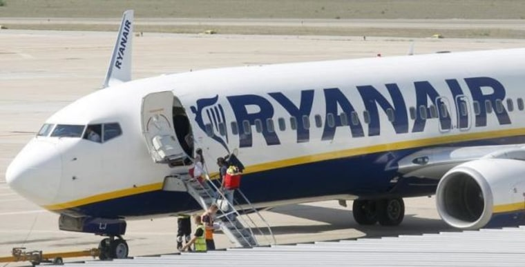 Passengers board a Ryanair plane parked at Girona airport