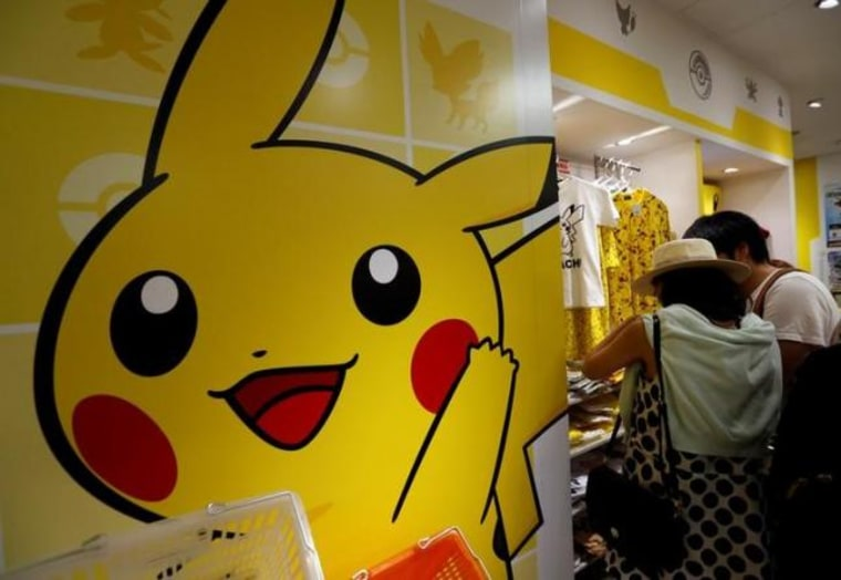 Customers look at goods of Pokemon at a shop in Tokyo