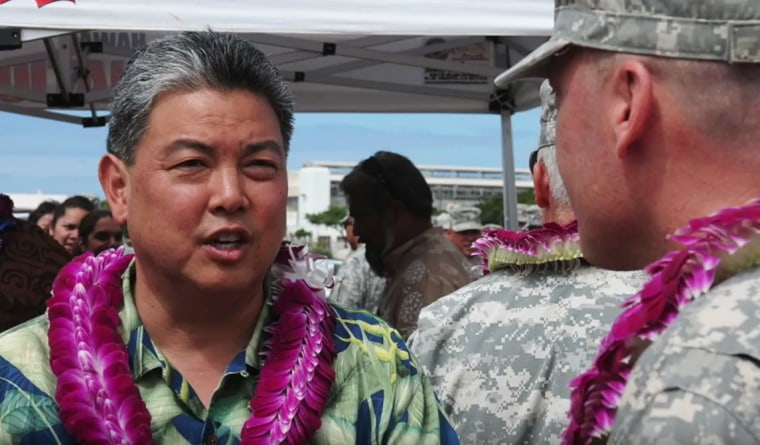 This screenshot from a tribute video for Rep. Mark Takai shows the light congressman speaking with service members.