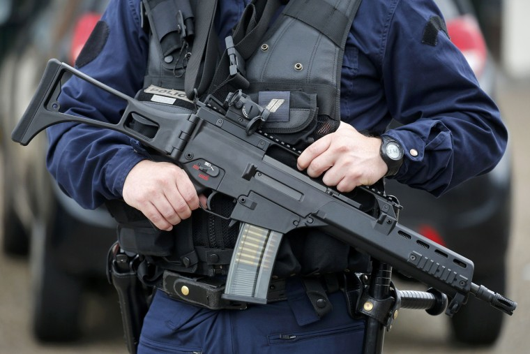 Image: A policeman holds a HKG36 assault rifle as he secures the position in front of the city hall after two assailants had taken five people hostage in the church at Saint-Etienne-du -Rouvray near Rouen in Normandy