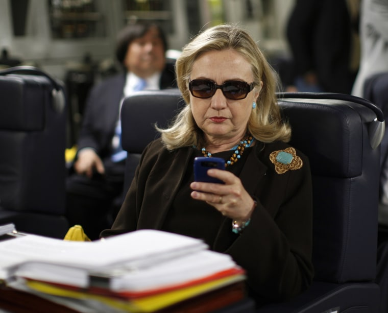 Then Secretary of State Hillary Clinton checks her Blackberry from a desk inside a C-17 military plane upon her departure from Malta, in the Mediterranean Sea, bound for Tripoli, Libya on Oct. 18, 2011.