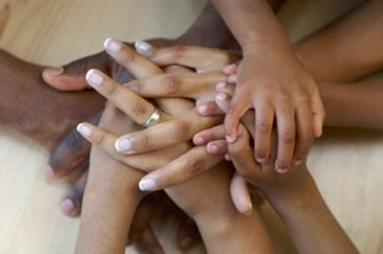 Hands of Black family in a pile.