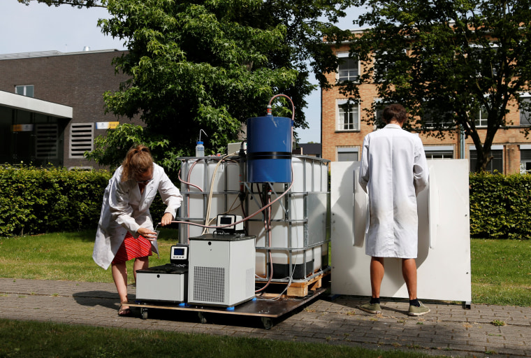 Image: Belgian scientists Vanoppen and Derese demonstrate the use of a machine that turns urine into drinkable water and fertilizer using solar energy, at the University of Ghent