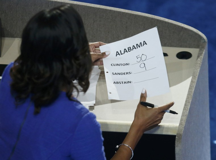 Image: A staff member holds the delegate vote count for Alabama at the Democratic National Convention in Philadelphia