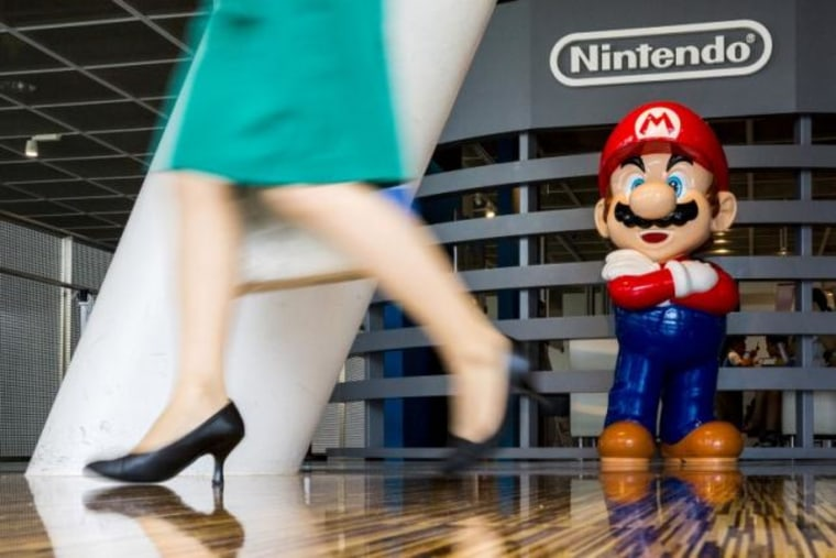 """Woman walks past figure of """"Mario"""" video game character at Nintendo centre in Tokyo"""