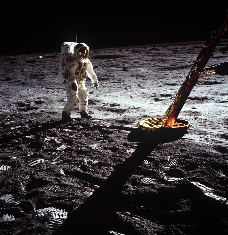 """Astronaut Edwin E. Aldrin Jr., lunar module pilot, walks on the surface of the moon near a leg of the Lunar Module during the Apollo 11 extravehicular activity (EVA). Astronaut Neil A. Armstrong, Apollo 11 commander, took this photograph with a 70mm lunar surface camera. The astronauts' bootprints are clearly visible in the foreground. While astronauts Armstrong and Aldrin descended in the Lunar Module (LM) """"Eagle"""" to explore the Sea of Tranquility region of the moon, astronaut Michael Collins, command module pilot, remained with the Command and Service Modules (CSM) """"Columbia"""" in lunar orbit (Photo Credit: NASA)."""