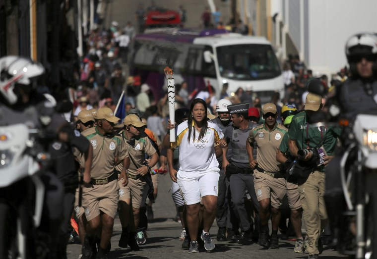 Image: Former volleyball player Santos carries the Olympic torch in the streets of Sao Luiz do Paraitinga