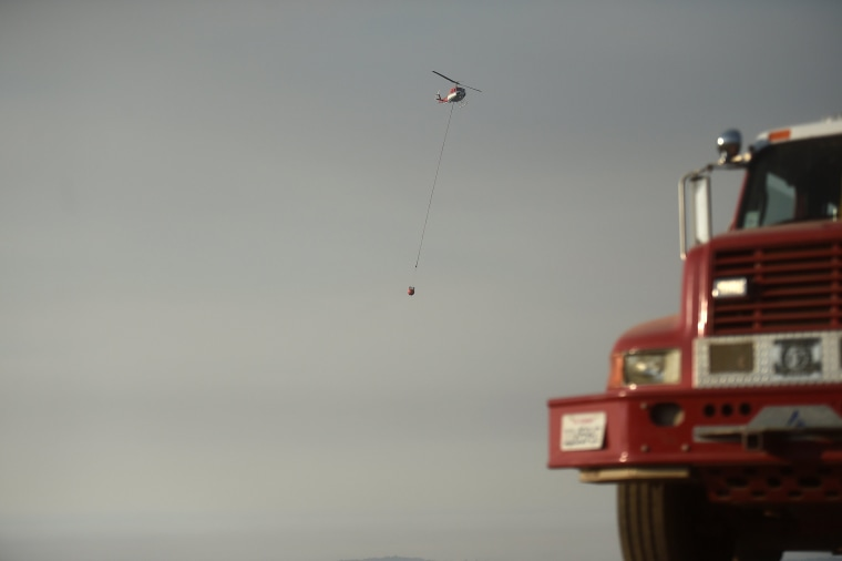 Image: A helicopter carries water to drop on the Soberanes Fire in Carmel Highlands
