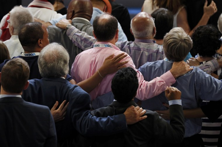 Image: Delegates reach out to one another during a tribute to fallen law enforcement officers at the Democratic National Convention in Philadelphia