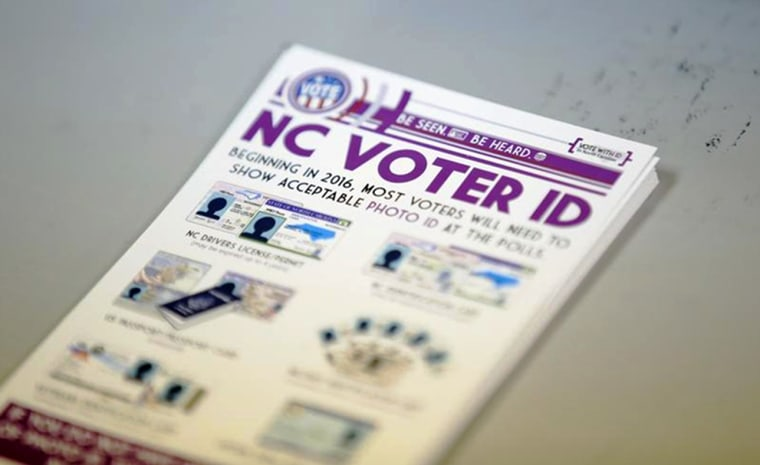 "A pile of government pamphlets explaining North Carolina's controversial ""Voter ID"" law sits on table at a polling station as the law goes into effect for the state's presidential primary in Charlotte, North Carolina, U.S. on March 15."