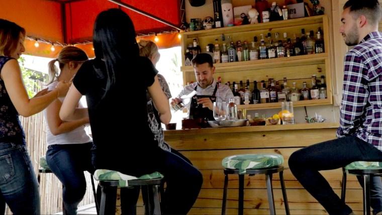 Gio Gutierrez entertaining guests in his backyard tiki bar.