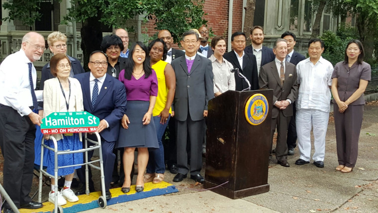 The Oh family and Philadelphia leaders during a ceremony dedicating In-Ho Oh Memorial Way. The woman behind the sign is In-Ho Oh's aunt.