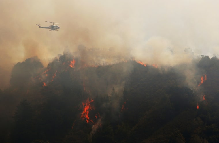 Image: A Cal Fire helicopter flies over Williams Canyon during the Soberanes Fire near Carmel Valley