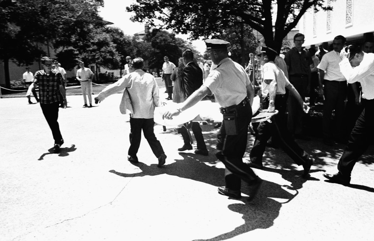 FILE: In this Aug. 1, 1966 file photo, one of the victims of Charles Joseph Whitman, the sniper who gunned down victims from a perch in the University of Texas tower, is carried across the campus to a waiting ambulance in Austin.