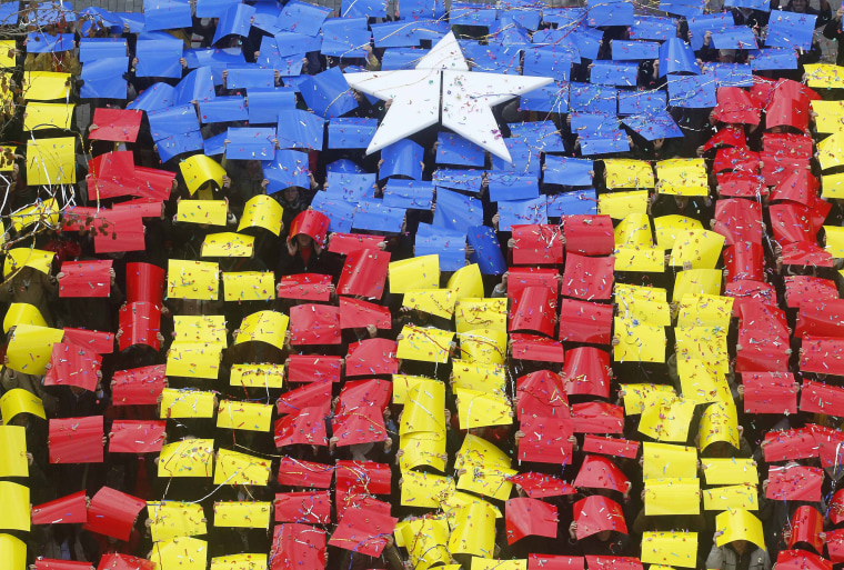 Image: People hold placards to form a giant Estelada, or Catalan separatist flag, in front of the Sant Feliu del Llobregat townhall, near Barcelona