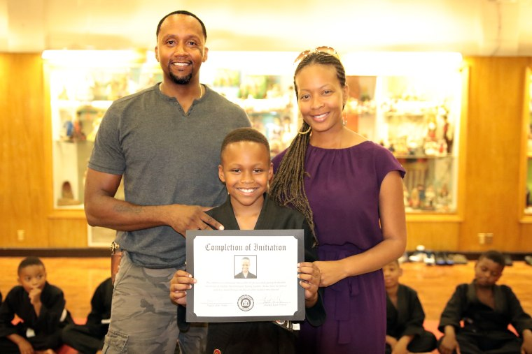 Bruce Collins III, with his parents after passing his initiation test.