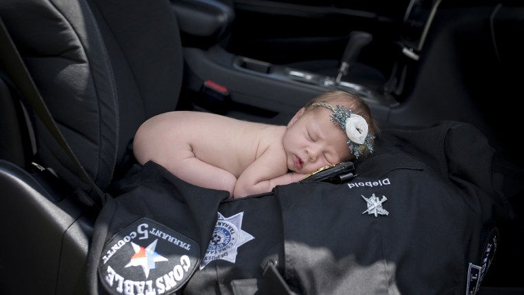 baby swaddled with police badge