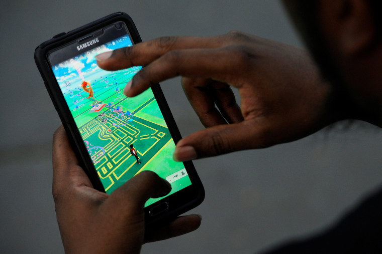 """Image: A man plays the augmented reality mobile game """"Pokemon Go"""" in New York City"""