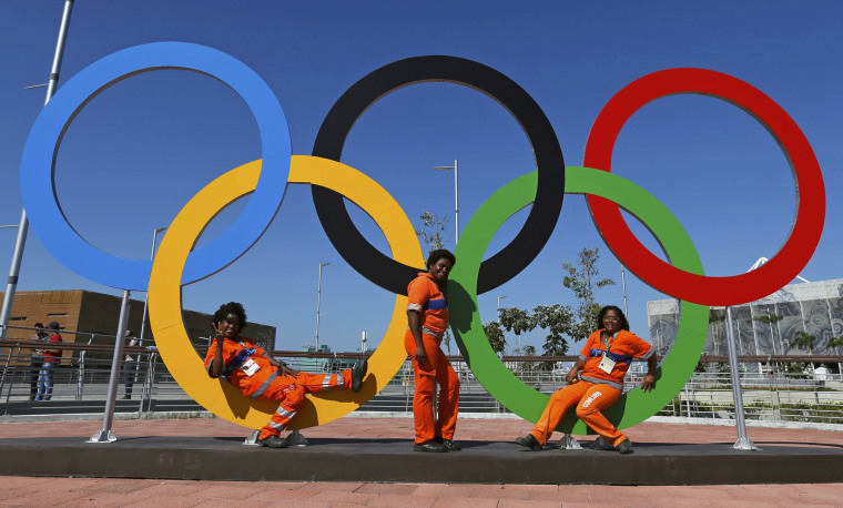 Image: Three cleaners pose in the rings at the Olympic Park in Rio de Janeiro