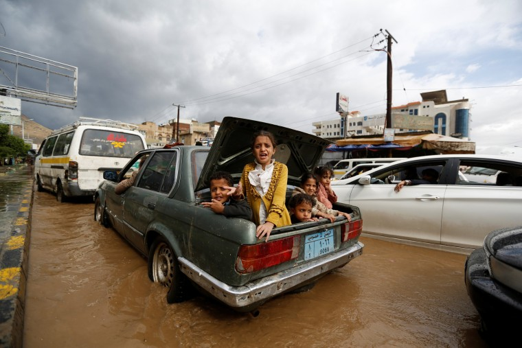 Image: Children ride in the trunk of a car on a flooded street in Sanaa, Yemen