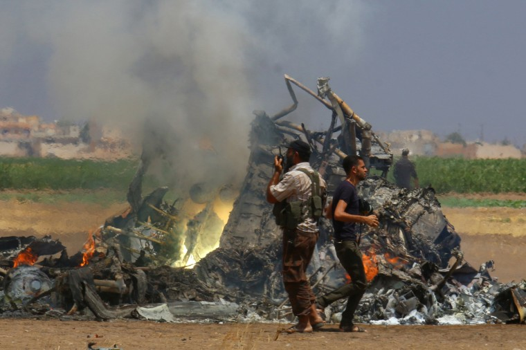 Image: Men inspect the wreckage of a Russian helicopter that had been shot down in the north of Syria's rebel-held Idlib province