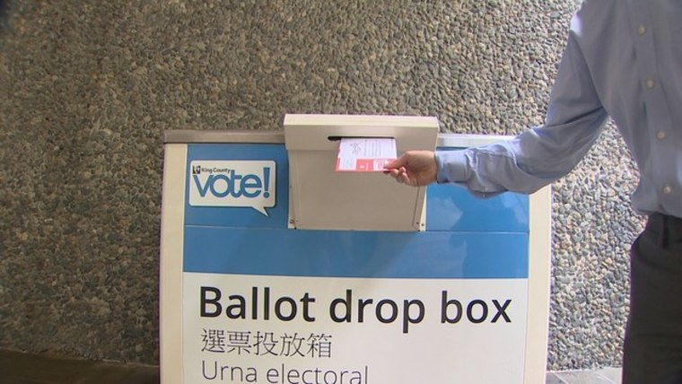 A Washington State voter deposits a ballot into a collection box ahead of the close of the state's primary election period Aug. 2.